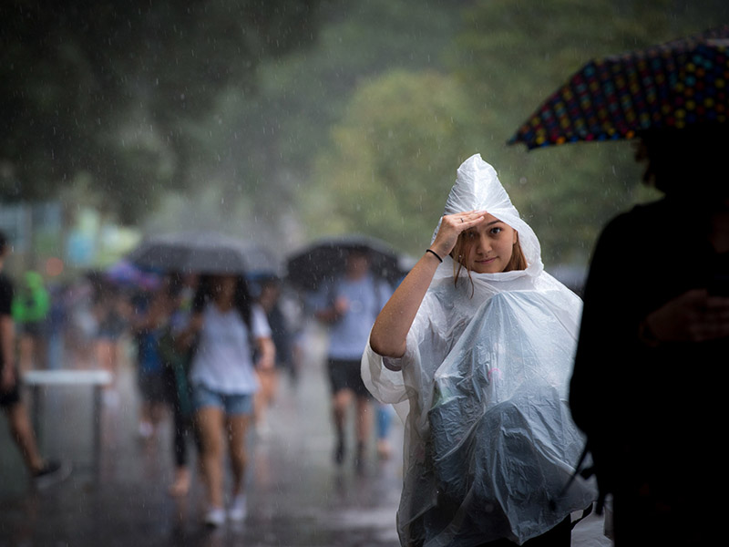 A Tulane senior peeks out from the protection of her rain poncho as she walks up McAlister Place during a downpour.